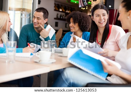 Young students discussing in cafe - stock photo