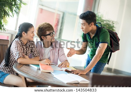 Young students discussing something with interest inside - stock photo