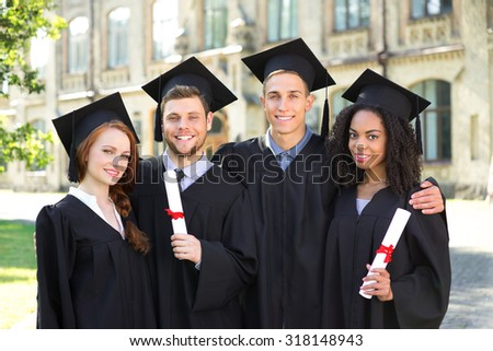 Young students dressed in black graduation gown. Campus as a background. Boys and girls smiling, hugging, holding diplomas and looking at camera - stock photo