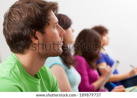 Young students during listening an interesting lecture - stock photo