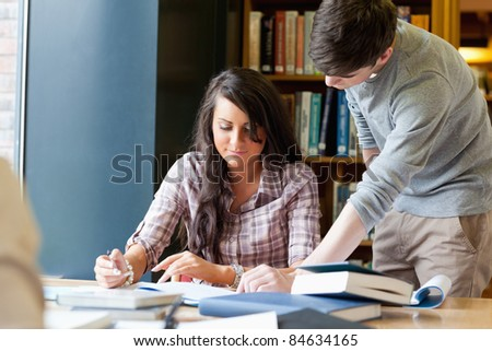 Young students working on a essay in a library - stock photo