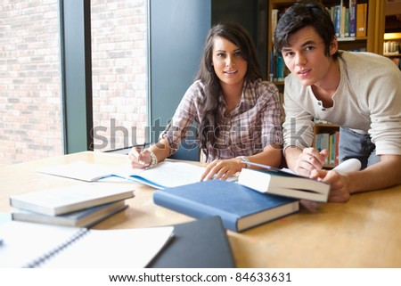 Young students working together in the library - stock photo