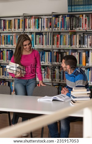 Young Students Working Together In The Library - Shallow Depth Of Field - stock photo