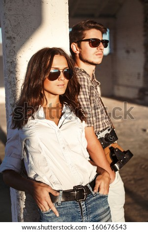 Young stylish beautiful fashion couple posing outdoor in summer. Young man with cute woman enjoying the sunset together in evening.  - stock photo