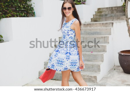 young stylish beautiful woman in blue printed dress, red bag, sunglasses, happy mood, fashion outfit, trendy apparel, smiling, summer, accessories - stock photo