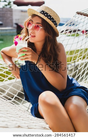 young stylish beautiful woman in pink sunglasses and straw hat, blue dress, drinking tropical cocktail blue hawaii sitting in hammock at resort pool, smiling happy, enjoying sunny summer day, vacation - stock photo