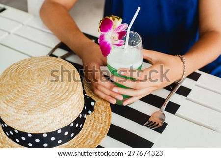 young stylish beautiful woman, straw hat drinking blue hawaii tropical cocktail sitting at resort cafe, enjoying warm summer day, vacation, close up hands holding glass, details, exotic flower - stock photo