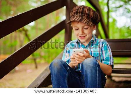 Young stylish boy browses internet on his mobile phone - stock photo