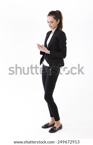 Young stylish Businesswoman using mobile phone. Isolated on white background. Full length Portrait of a Caucasian brunette female model. - stock photo