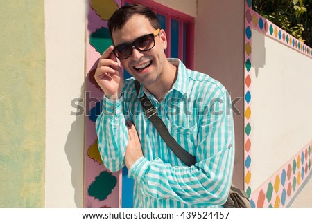 Young stylish confident happy laughing handsome man model in blue t-short in sunglasses. color pattern background - stock photo