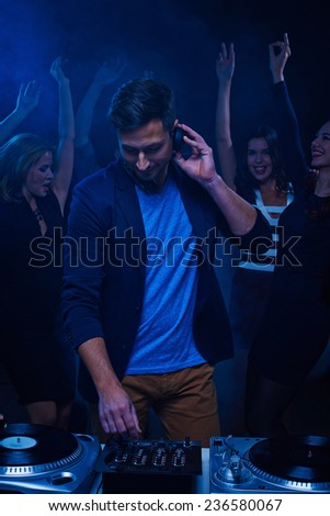 Young stylish deejay at dancing party in night club - stock photo