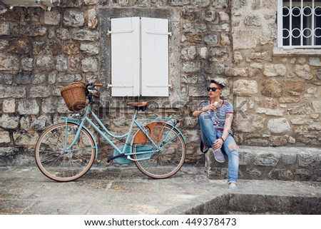 Young stylish girl drinking coffee while resting from her bike trip. Coffee break, then cycle.  - stock photo