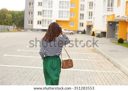 Young stylish girl in a long green skirt and a striped T-shirt in the yard. Street fashion look - stock photo