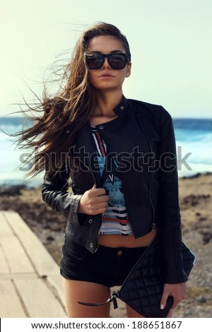 Young stylish girl in shorts and leather jacket posing at wind against sea. Fashion portrait - stock photo