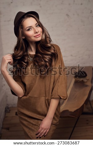 Young stylish girl wearing brown dress and hat standing near table in simple loft interior, looking at you and smiling. Pretty woman. - stock photo