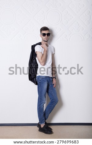 Young stylish guy with glasses, jeans and leather jacket standing on a white wall with ornament. Portrait in full growth. - stock photo