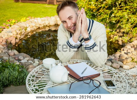 Young stylish handsome man in bright confidential clothes work at  iron table with computer & teapot against country garden. - stock photo