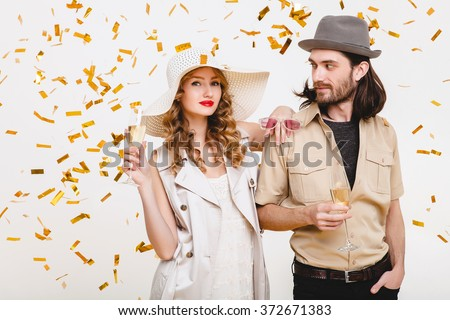 young stylish hipster couple in love, holding glasses and drinking champagne, toasting, celebrating disco party, having fun, golden confetti, trendy apparel, luxury cruise style, white background - stock photo