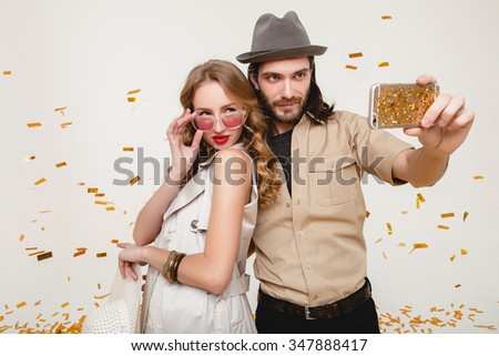 young stylish hipster couple in love making self photo, celebrating happy carnival disco party, having fun, golden confetti, holding phone, trendy apparel, cool outfit, resort style, white background - stock photo
