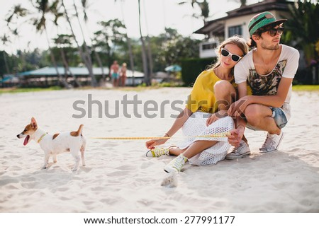 young stylish hipster couple in love walking playing dog puppy jack russell in tropical beach, white sand, cool outfit, romantic mood, having fun, sunny, man woman together, horizontal, vacation - stock photo