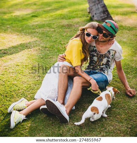 young stylish hipster couple in love with a dog puppy jack russel, tropical park, smiling and have fun during their vacation, sunglasses, cap, yellow and printed shirt, romance, lay on grass in park - stock photo