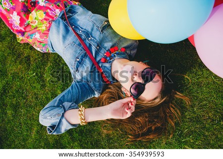 young stylish hipster teen girl happy, bubblegum, lying on grass in park, air balloons birthday party, cool accessories, sunglasses, colorful, having fun, denim shirt, fashion trend summer outfit - stock photo