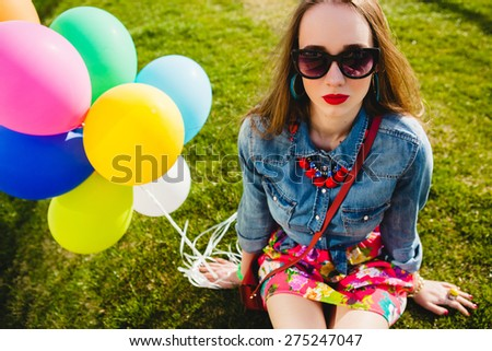 young stylish hipster teen girl happy, park, air balloons birthday party, cool accessories, red lipstick makeup, colorful, sunny, have fun, sitting, grass, denim shirt, flower printed skirt sunglasses - stock photo