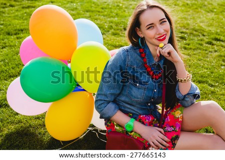 young stylish hipster teen girl happy smiling, park, air balloons birthday party, cool accessories, red lipstick makeup, colorful, sunny, have fun, sitting on grass, denim shirt, braces, sunny - stock photo