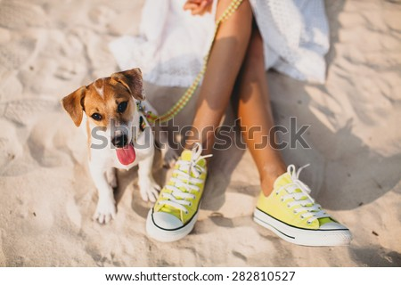 young stylish hipster woman playing dog puppy jack russell in tropical beach, cool outfit, romantic mood, having fun, sunny, horizontal, vacation, lying on the sand, shoes close up - stock photo