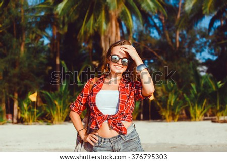 young stylish hipster woman traveling around the world, sitting on the pier, aviator sunglasses, hipster girl, vacation, backpack, denim shirt, happy, tropical island lagoon - stock photo