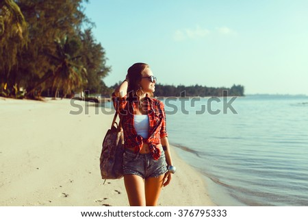 young stylish hipster woman traveling around the world, sitting on the pier, aviator sunglasses, headphones, listening to music, vacation, backpack, denim shirt, happy, tropical island lagoon - stock photo
