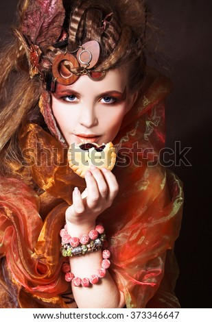 Young stylish lady with artistic make-up and autumn leafs in her hair and  with cake - stock photo