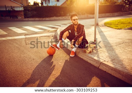 Young stylish man in sunglasses with a basketball and skateboard sitting on a city street at sunset light - stock photo