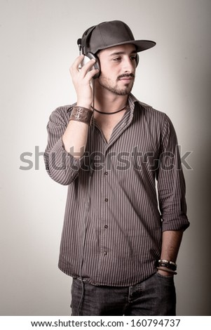 young stylish man listening to music on gray background - stock photo