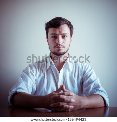 young stylish man with white shirt behind a table - stock photo