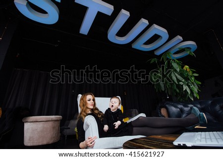 Young stylish  mother with her adorable baby girl in  hipster cafe. A working fashion mom and toddler. Hugging her daughter sitting in a chair. successful mom legs shoes on desk, funny yawning baby - stock photo