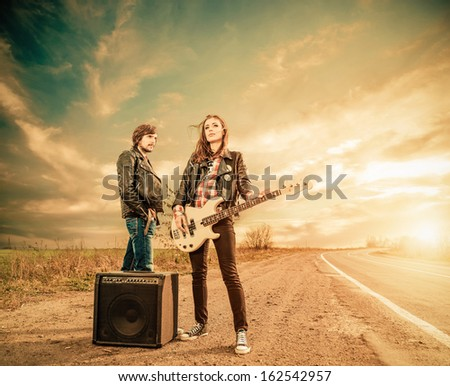 young stylish musicians on a road to horizon - stock photo