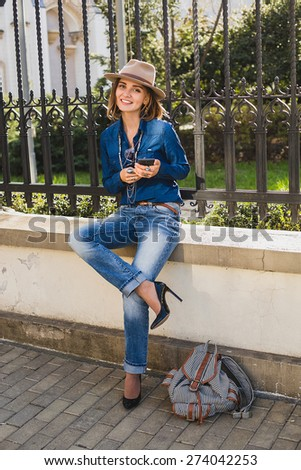 young stylish pretty happy woman smiling and holding phone, dressed in denim shirt and jeans, high heel shoes, with hat and backpack, sunny day, good weather, city street, accessories - stock photo