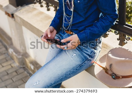 young stylish pretty woman, dressed in denim shirt and jeans, hat and backpack, sunny day, good weather, city street, vacation europe, travel, close up of hands holding a phone, detail - stock photo