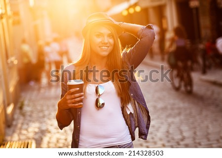 Young stylish woman drinking coffee to go in a city street - stock photo