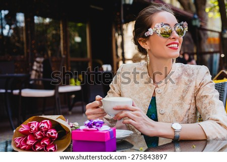 young stylish woman, fashion sunglasses sitting in cafe, holding drinking cup cappuccino, smiling, enjoying warm, presents, tulips, happy birthday party, city street, boho outfit, europe vacation - stock photo