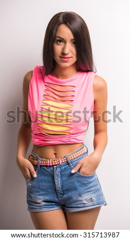 Young stylish woman is looking at the camera on grey background. - stock photo