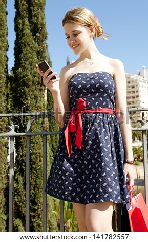 Young stylish woman using a smartphone while standing on a city bridge, holding shopping paper bags during a sunny day with a blue sky, smiling. - stock photo