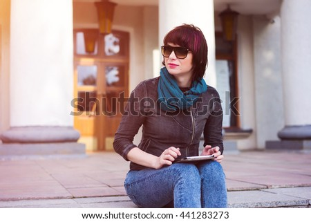 Young stylish woman using tablet outdoor. Student sitting on the college staircase. - stock photo