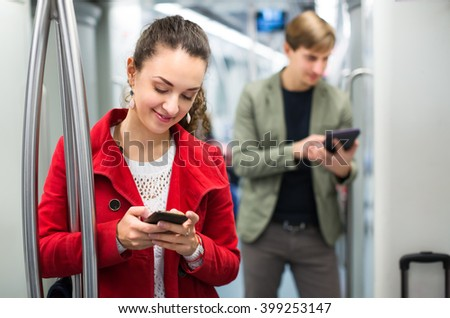 Young subway passengers busy with modern phones and tablet  - stock photo