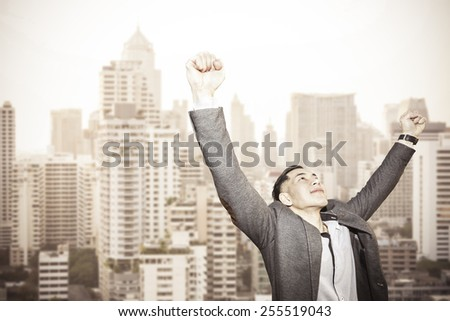 young successful asian businessman with urban background - stock photo