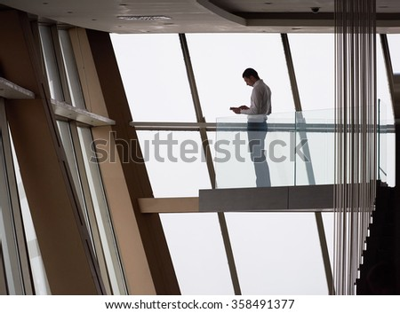 young successful business man in penthouse working on tbalet,  modern bright duplex office apartment interior  with staircase and big windows - stock photo