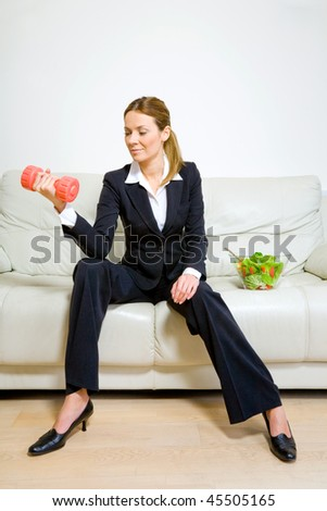 Young successful business woman with dumbbells and bowl of green salad - stock photo
