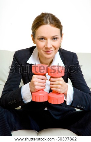 Young successful business woman with dumbells - stock photo