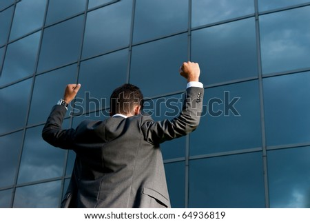 Young successful businessman celebrating a goal on a modern building background - stock photo